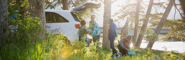 Family Unpacking Car At Campsite
