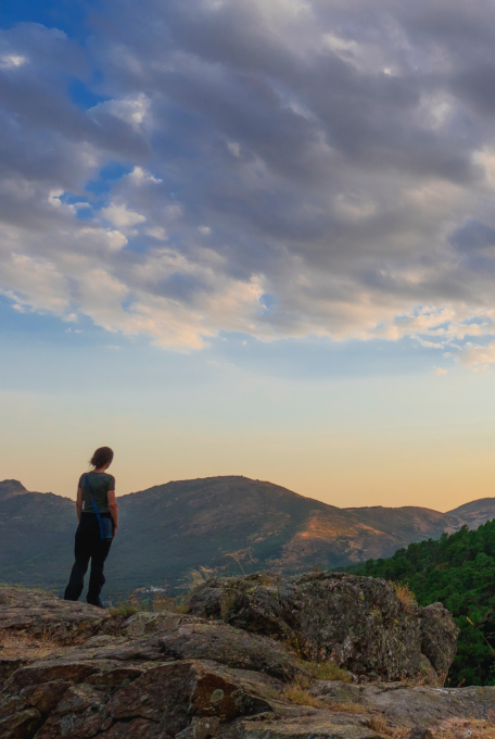 Rear View Of A Woman On A Rocks Watching Sierra De Guadarrama. Madrid, Spain. Mountains At Sunset With Clouds